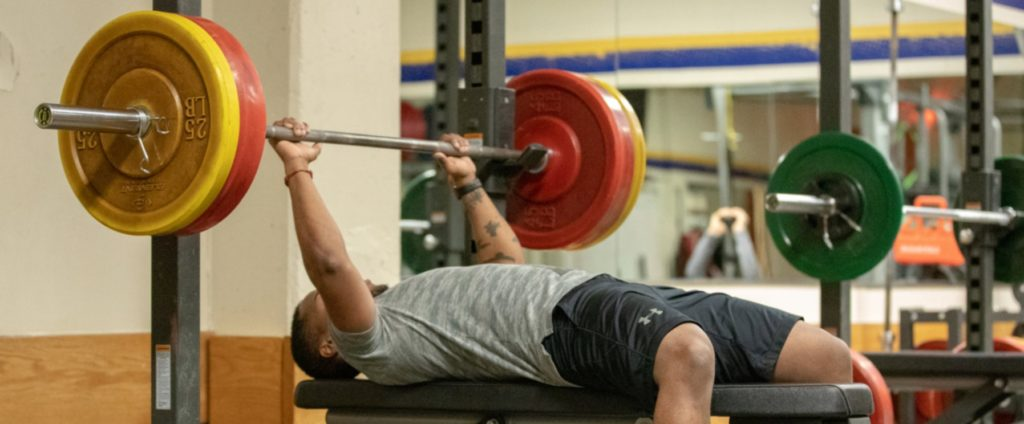 A man working out. He is lifting weights.